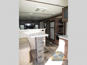 The Keystone 32RDDS Travel Trailer features a spacious kitchen, huge dinette counter, and rear entertainment lounge.
