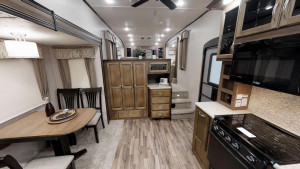 The Coachmen Chaparral 370FL has a huge kitchen area and three space living separating the living room, kitchen, and bedroom.
